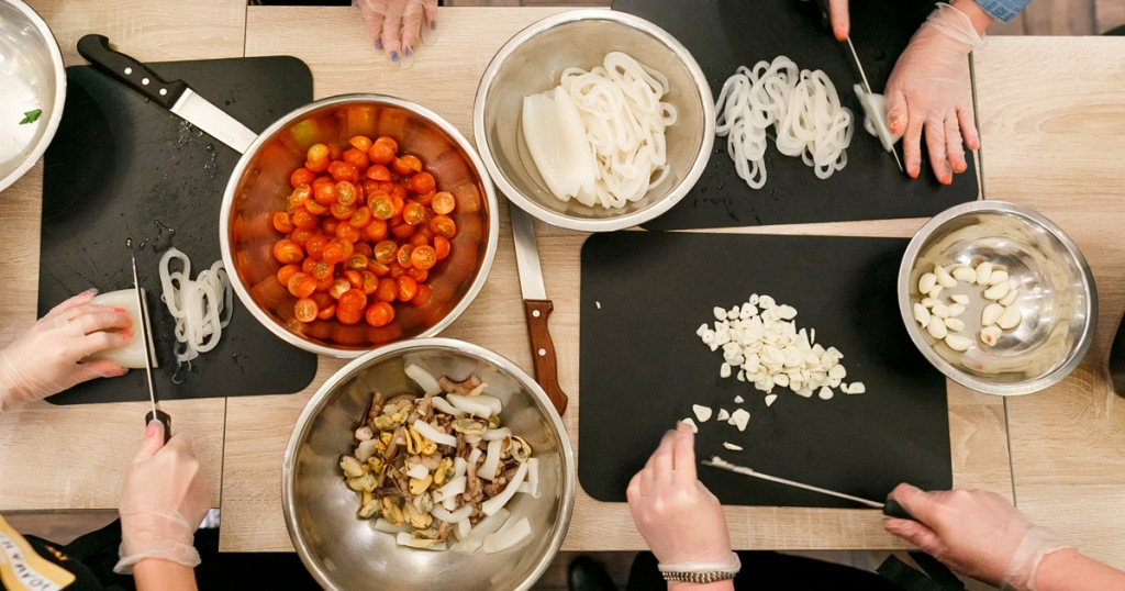people wearing gloves chopping up ingredients like onions, garlic, and tomatoes and placing them in metal bowls