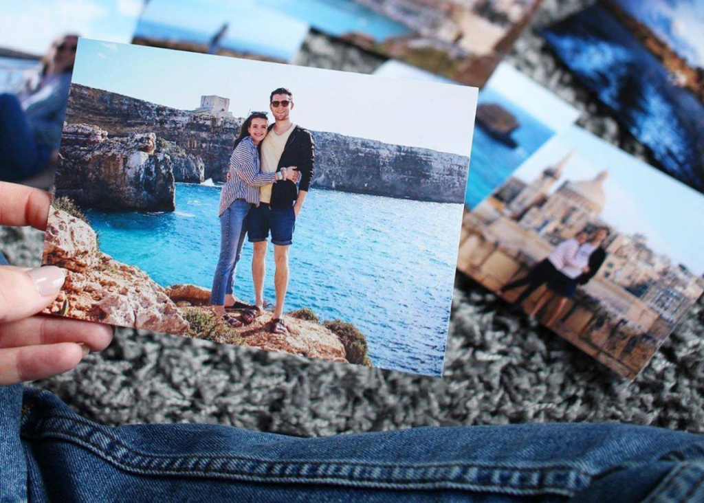 woman holding vacation photos