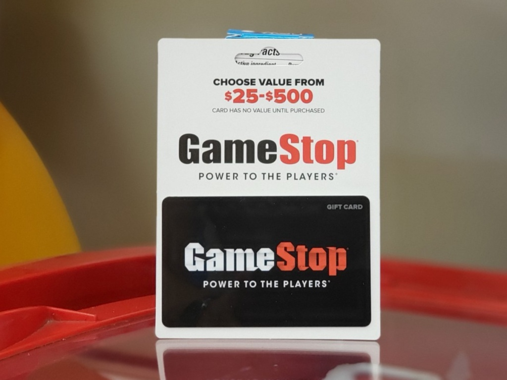 GameStop gift card standing on red table