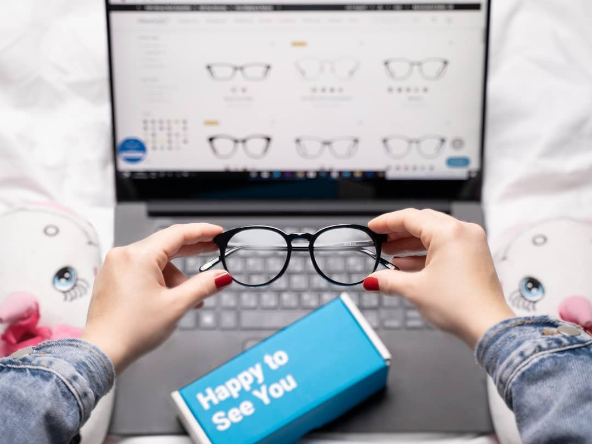 woman holding pair of black glasses in front of laptop