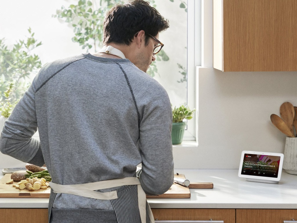 man looking at a Google Nest Hub on his counter