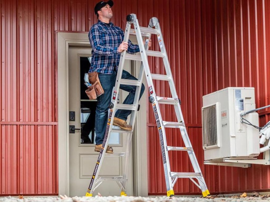 man at the top of an 18 foot ladder in front of a shed