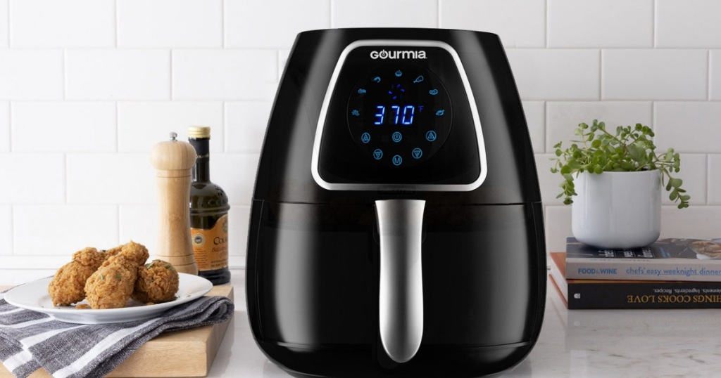 black air fryer with digital display sitting on kitchen counter next to fried chicken legs