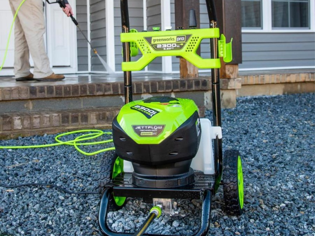 man using green power washer outside home