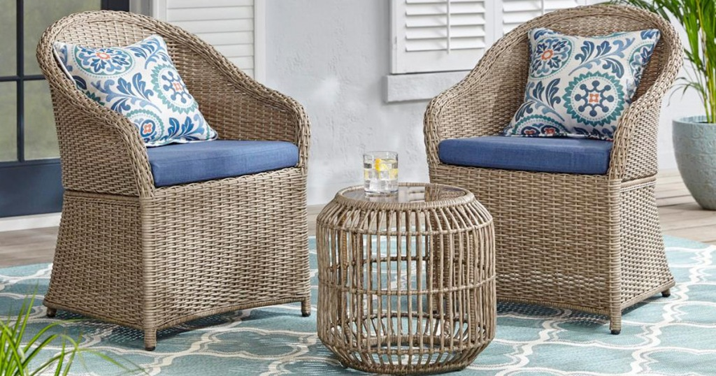 two picker patio chairs with blue cushions and matching wicker patio table