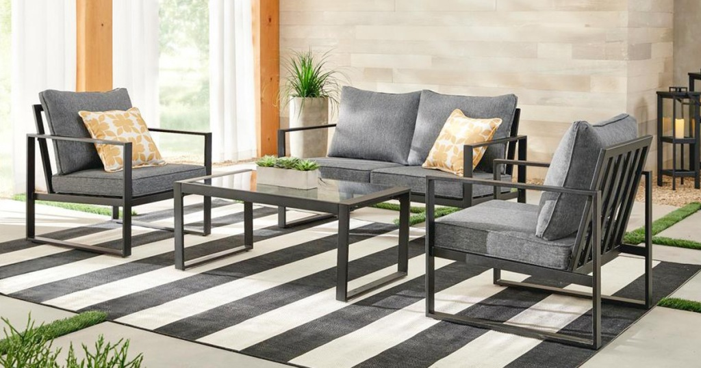 grey 4 piece patio set with black steel frame on a black and white striped rug