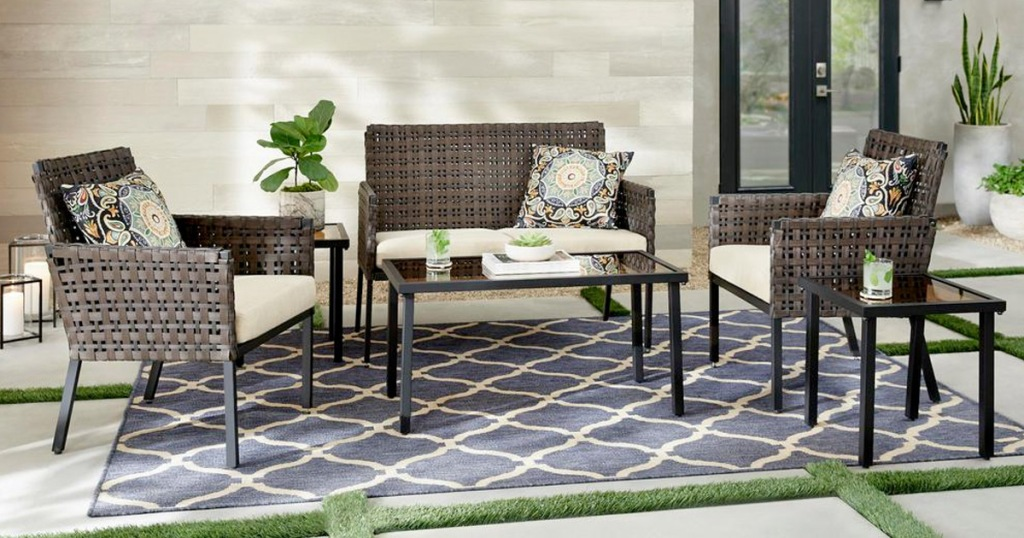 brown wicket patio set with beige cushions on a blue outdoor rug