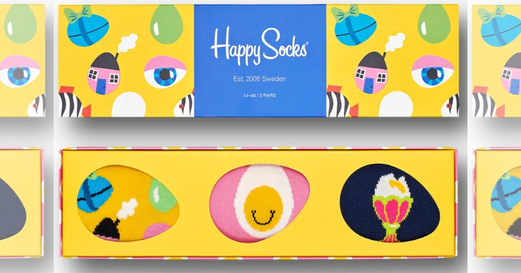 rectangle shaped gift box from happy socks with three pairs of socks inside with egg shaped cut out windows to see the socks. one sock is pink with smily eyes, one is yellow with decorative eggs, one is navy with sundaes on them