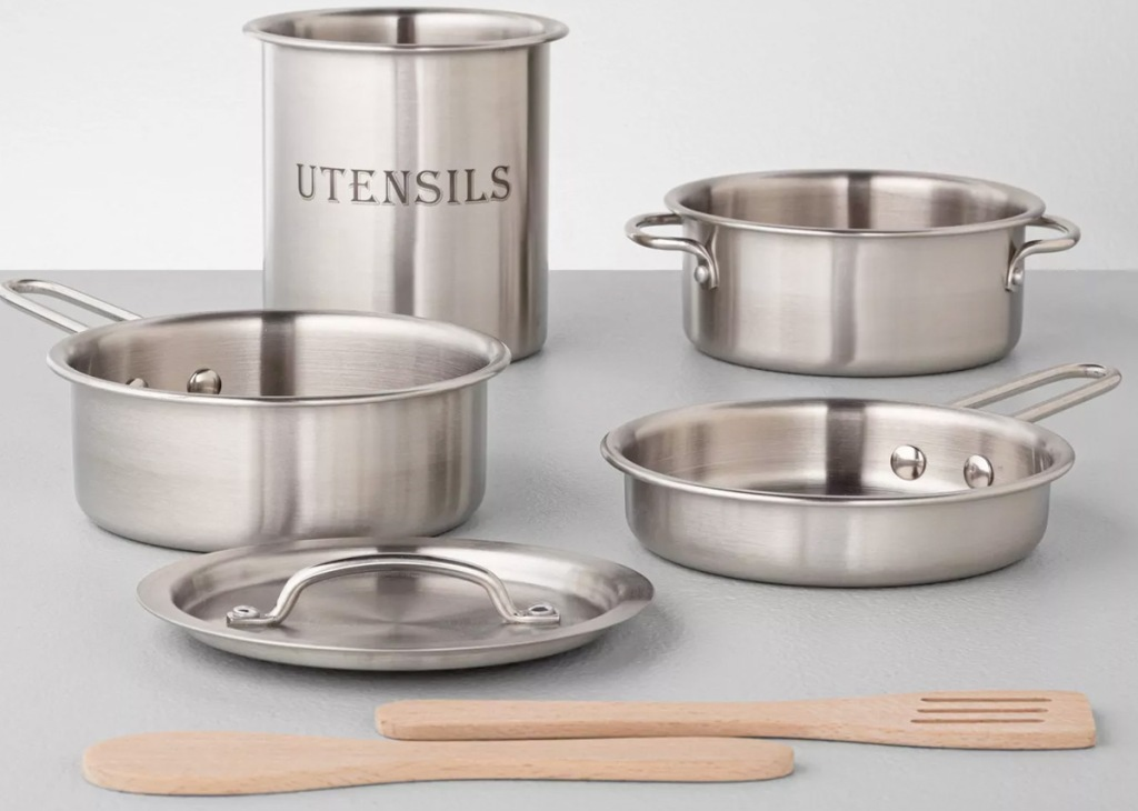 kids cookware set with pots, pans, lids, and wooden spoons on grey table