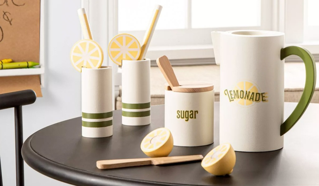 kids wooden lemonade set with pitchers, glasses, lemons, and wooden spoons sitting on black table