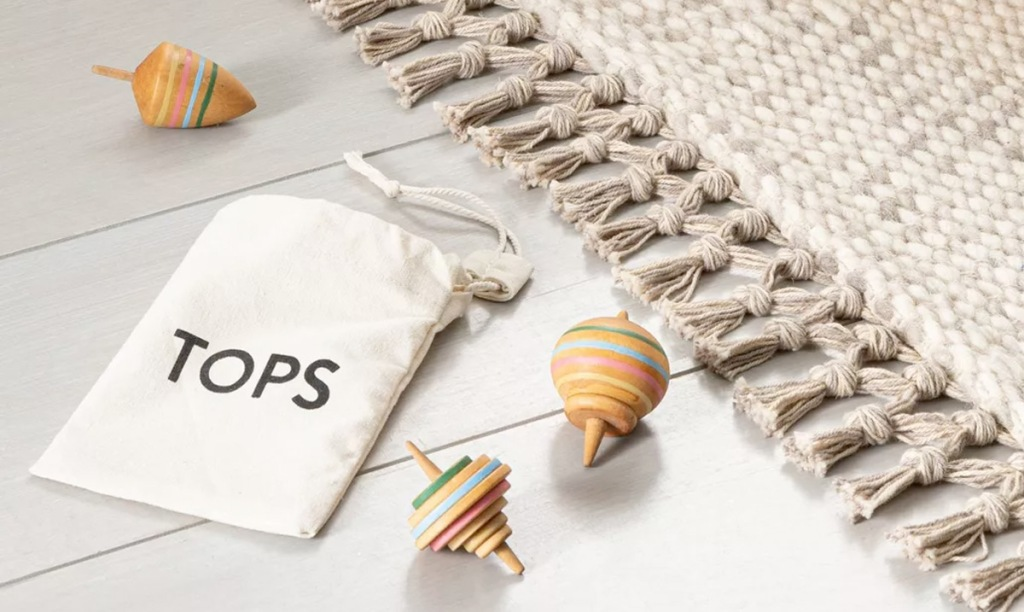 three wooden striped spinning tops laying on floor with white drawstring bag labeled tops