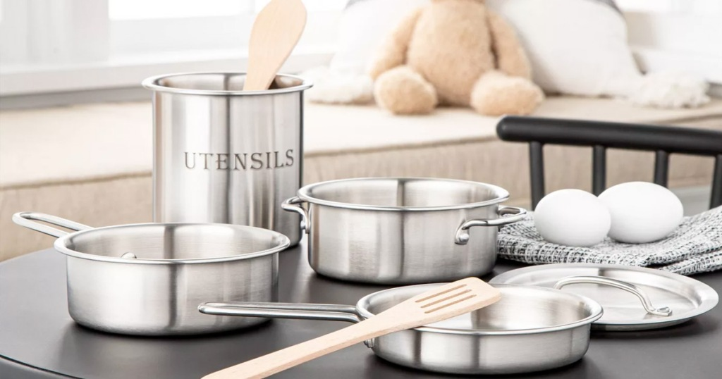 kids cookware set with pots, pans, lids, and wooden spoons on a black table in a playroom