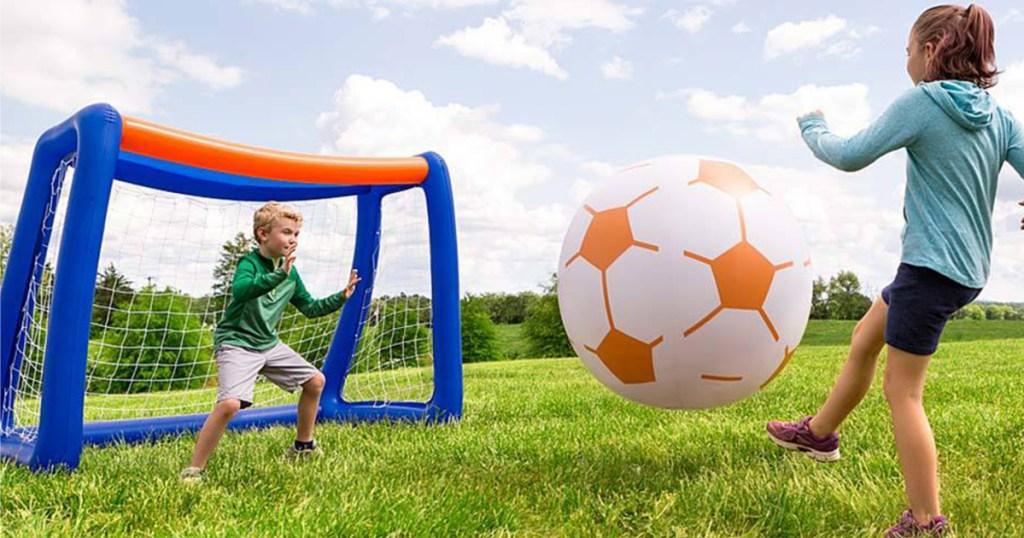 kid kicking inflatable soccer ball into goal