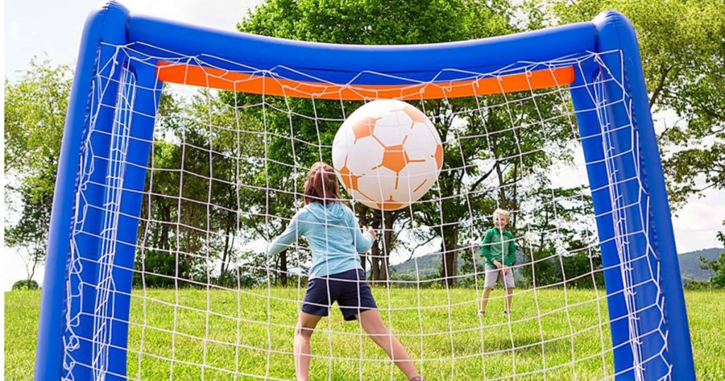 kids playing soccer with large inflatable ball and goal