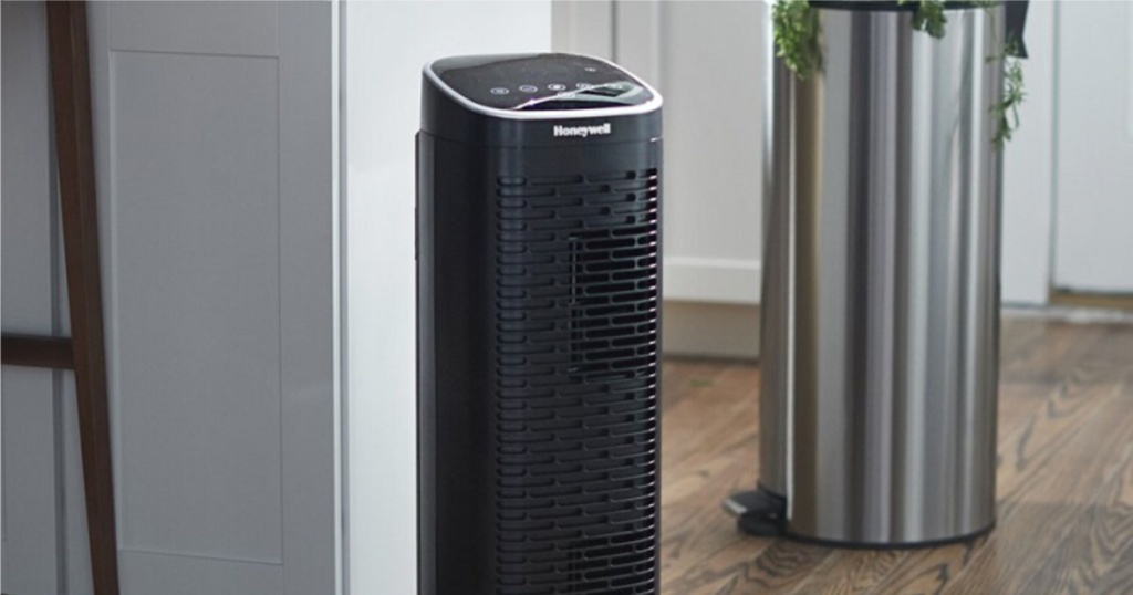 black air purifier in kitchen next to trash can