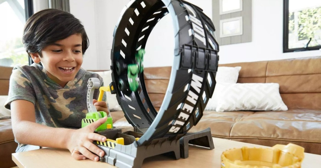 boy playing with Hot Wheels Monster Truck Epic Loop Challenge Play Set with Truck and Car on table with green car going around the loop