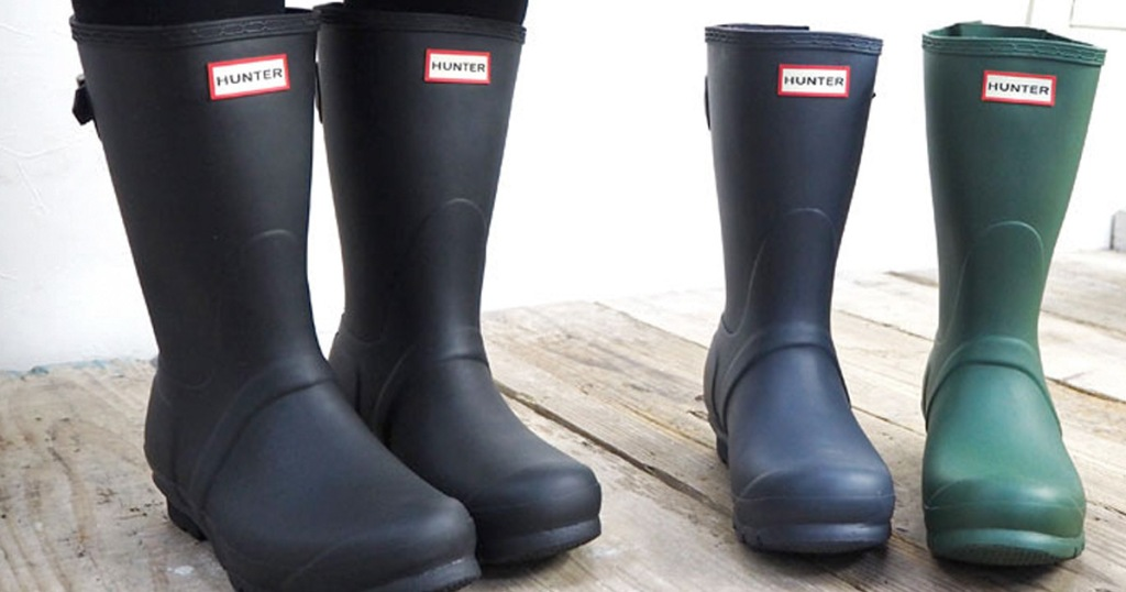 pair of short black matte finish hunter rain boots with blue and green boots next to them