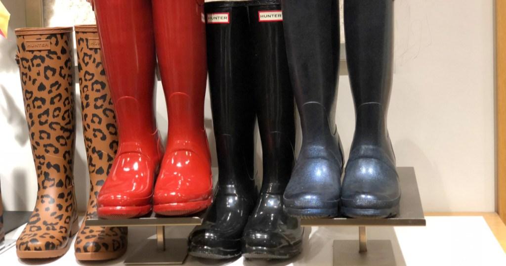 shelf display of various colors of glossy hunter brand rain boots