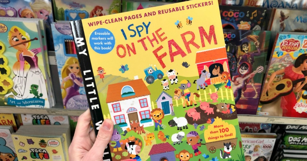 Woman's hand holding a farm-themed sticker book