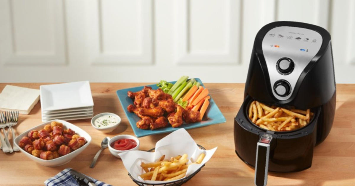 air fryer with basket pulled out and fries in the basket with wings fries and other food nearby