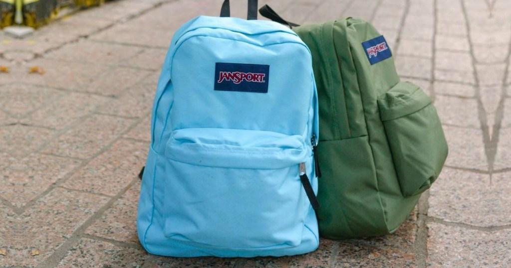 2 Jansport backpacks on sidewalk