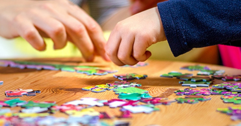 people putting together jigsaw puzzle on wooden table