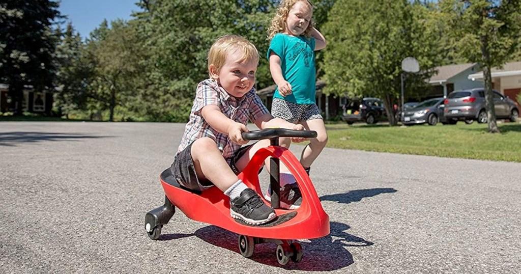 anak kecil bermain di mobil ayunan merah dan hitam di lingkungan sekitar