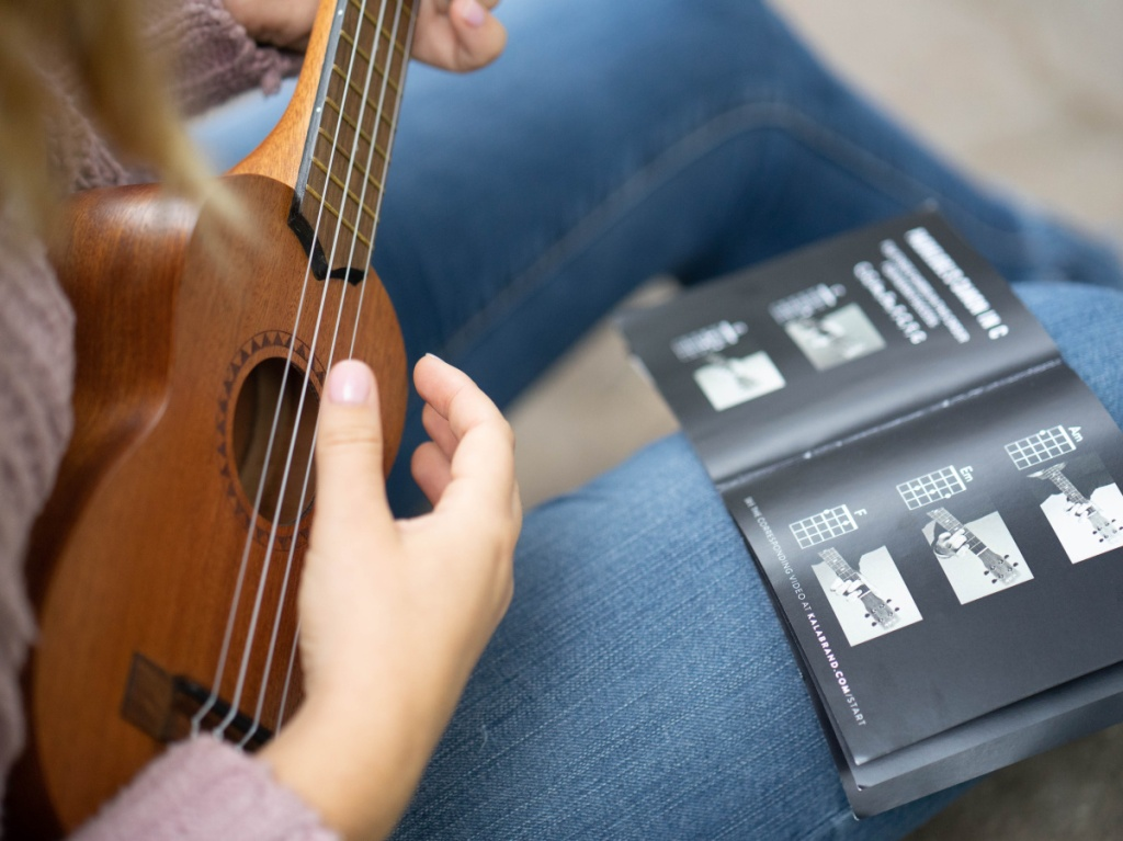 woman using brown ukulele and black instructional booklet