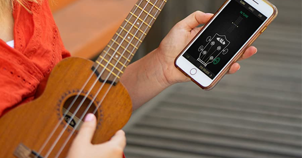 woman in orange shirt holding cell phone and brown ukulele