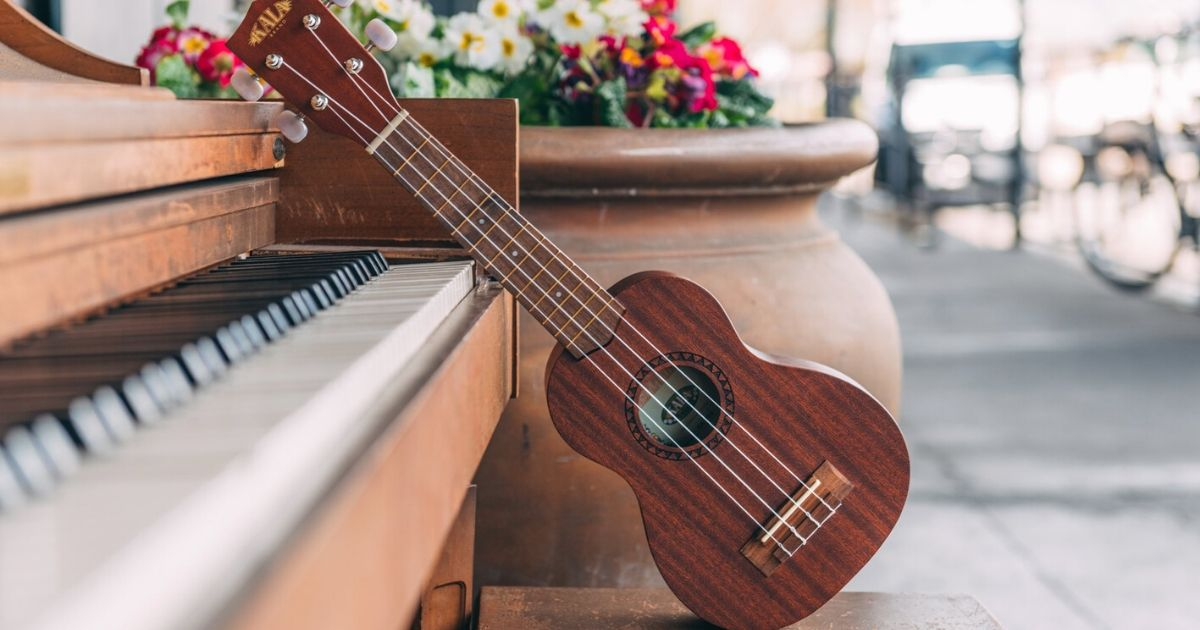 kala ukulele on bench leaning on a piano in front of a large potted plant with flowers