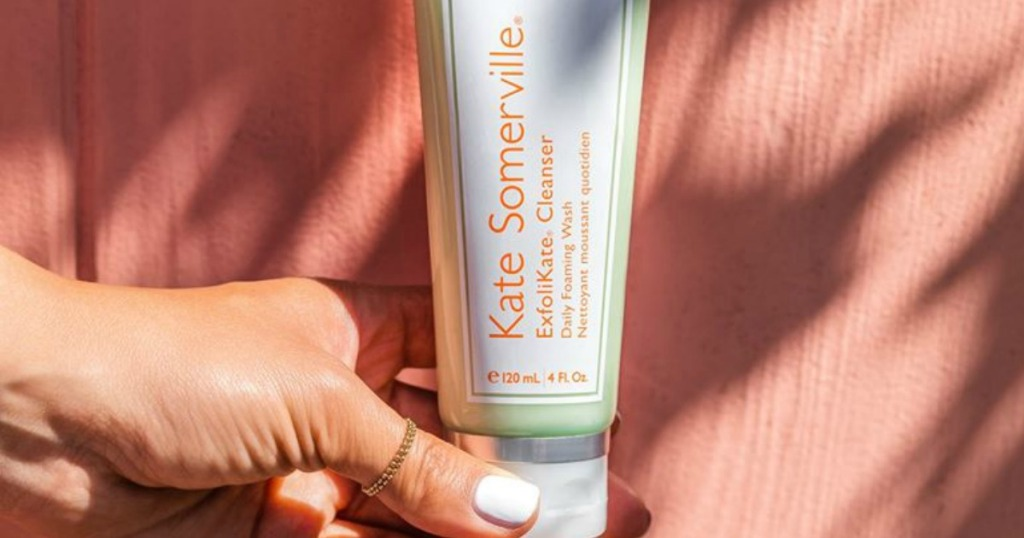 woman holding Kate Somerville Exfolikate cleanser