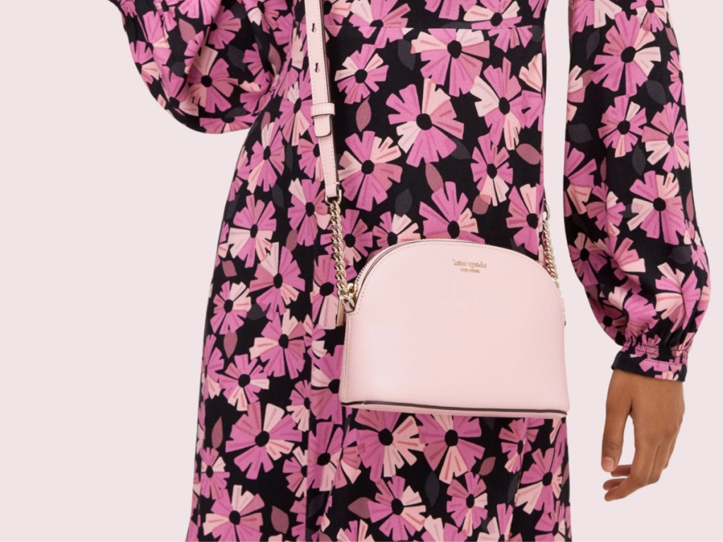 woman wearing flowery dress carrying pink crossbody bag
