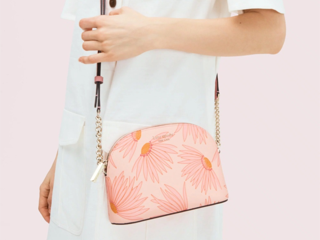 woman wearing white dress carrying pink flowered crossbody bag