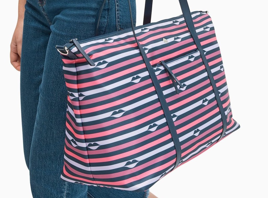 woman carrying a large striped weekender bag
