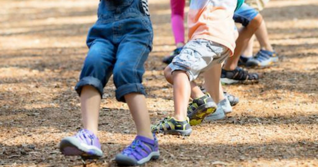 kids running on bark playground wearing leather sandals