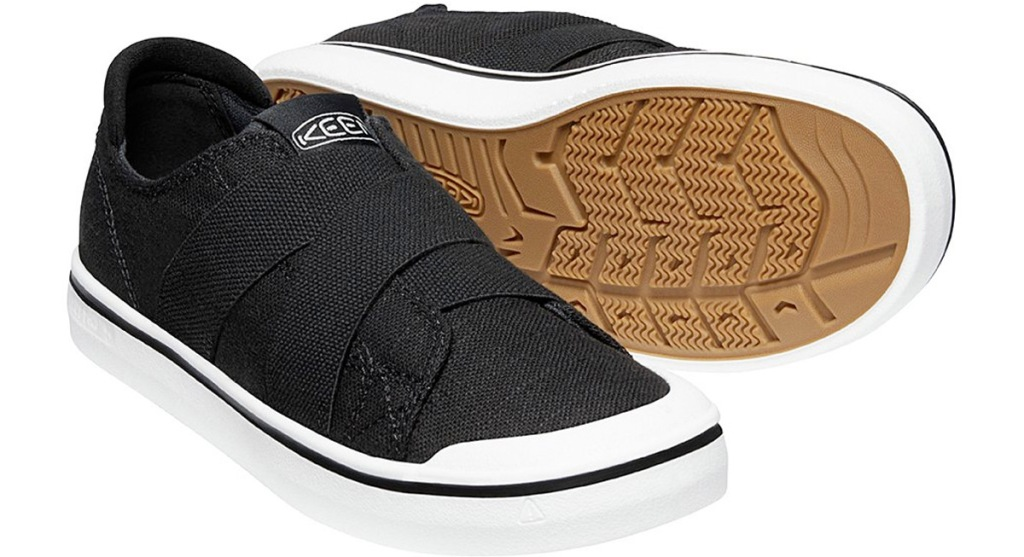 black canvas slip on sneakers with elastic straps across tongue