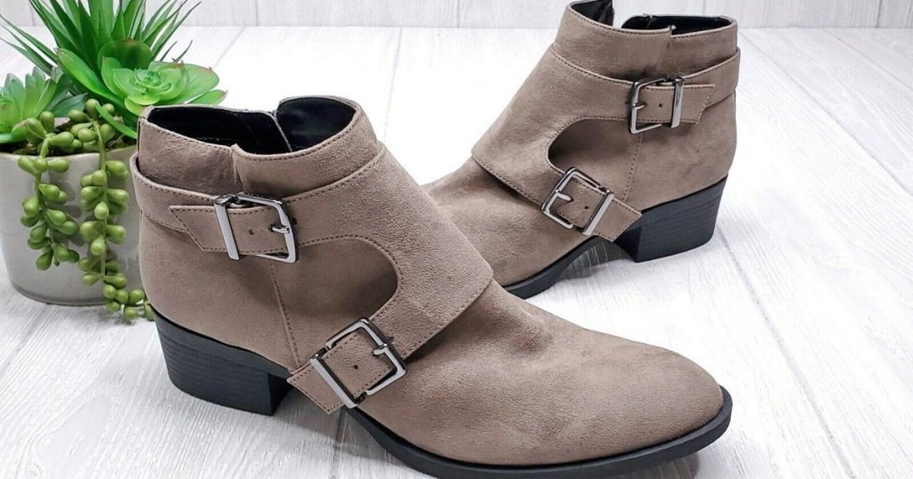 pair of taupe colored suede womens booties with two buckles on the side