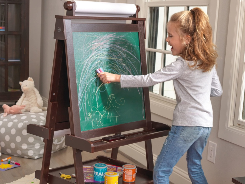 Little girl drawing on an easel
