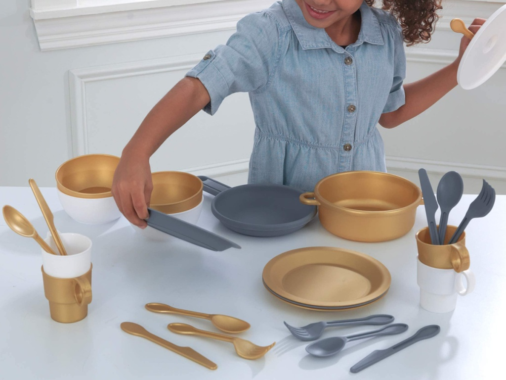 little girling playing with kitchen playset