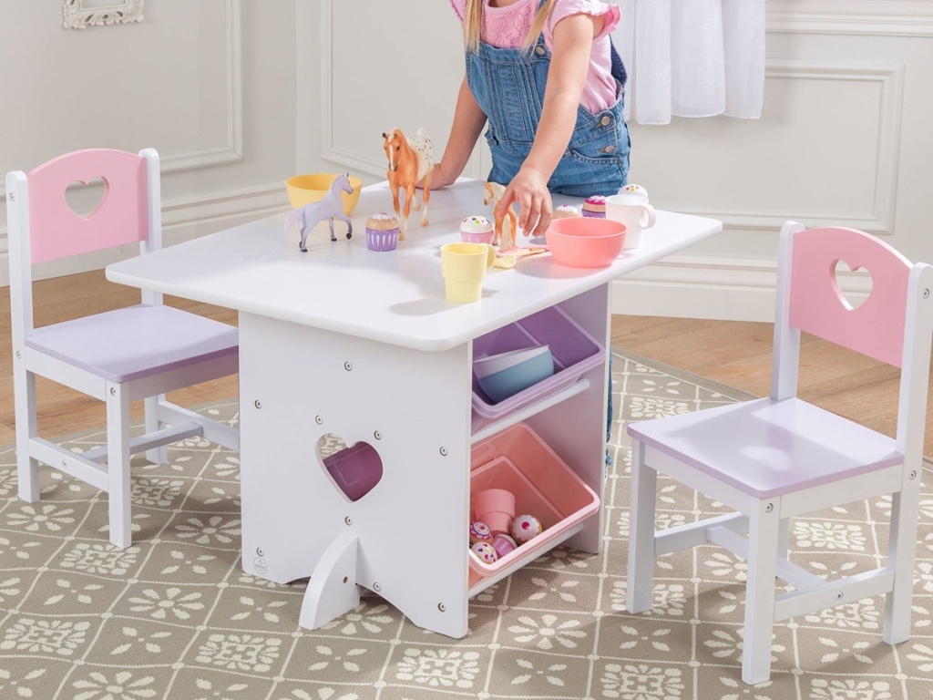little girl playing at white table
