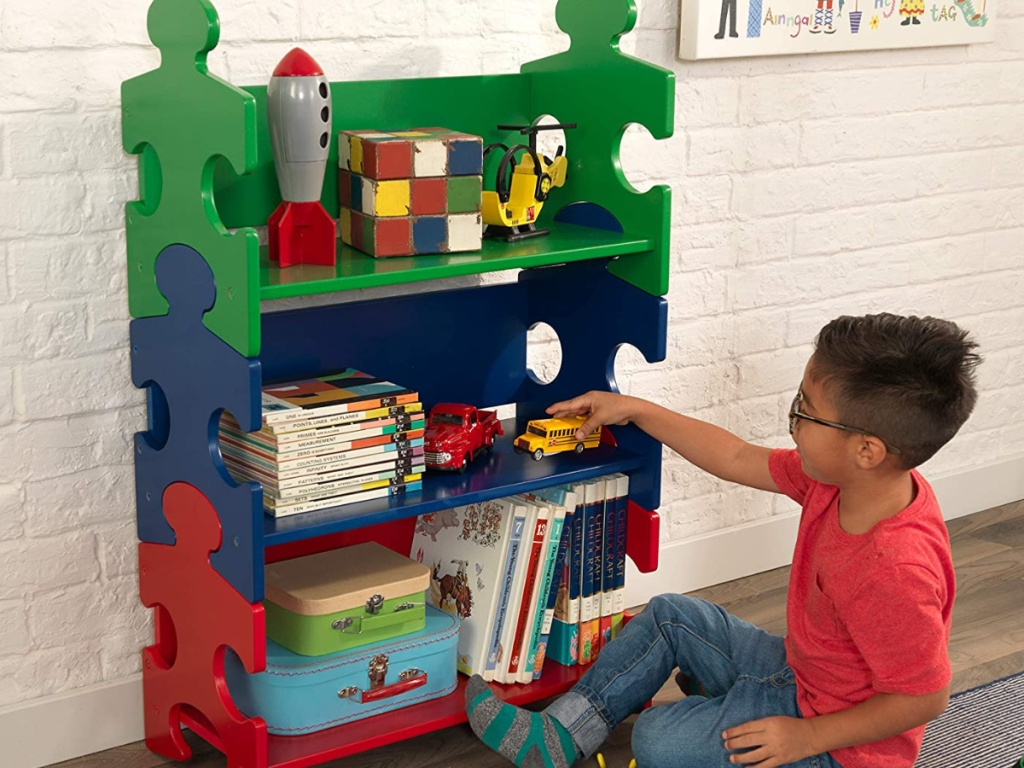 little boy sitting in front of puzzle shaped bookshelf