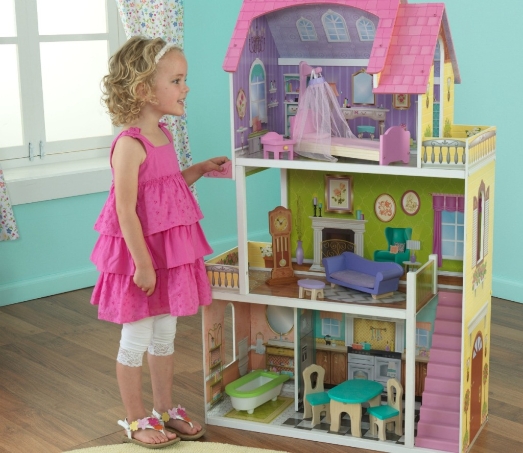 little girl standing next to a large dollhouse