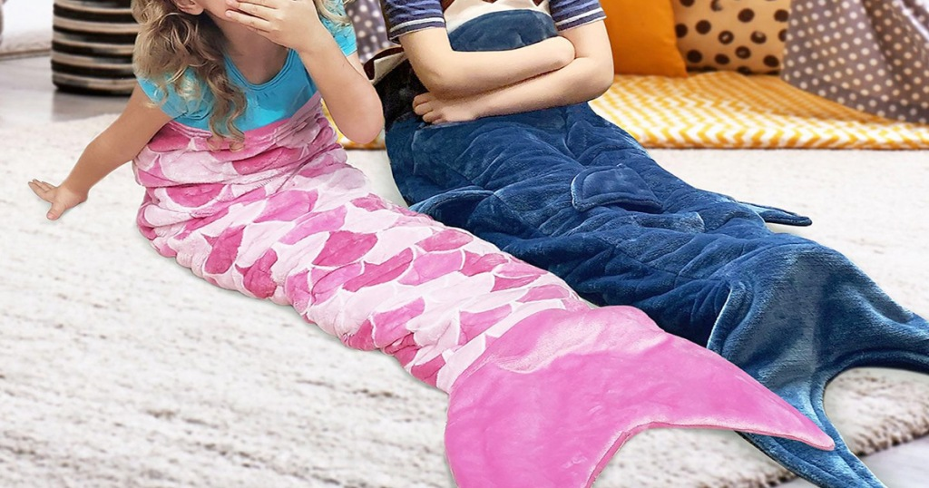 kids sitting on floor under pink mermaid and blue shark tail shaped blankets