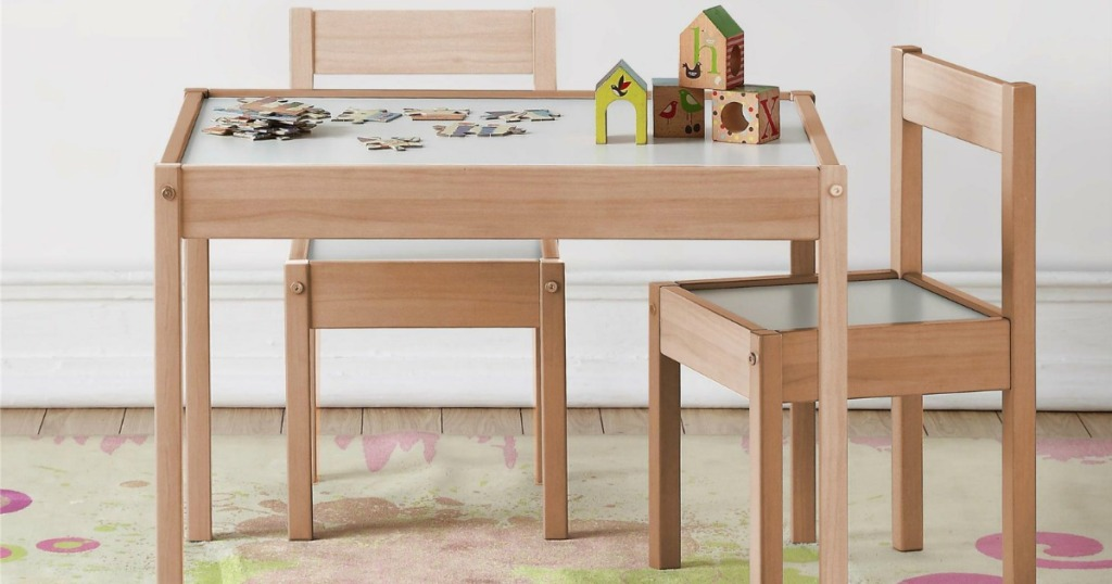 Light wooden table with kids sized chairs and puzzle on top