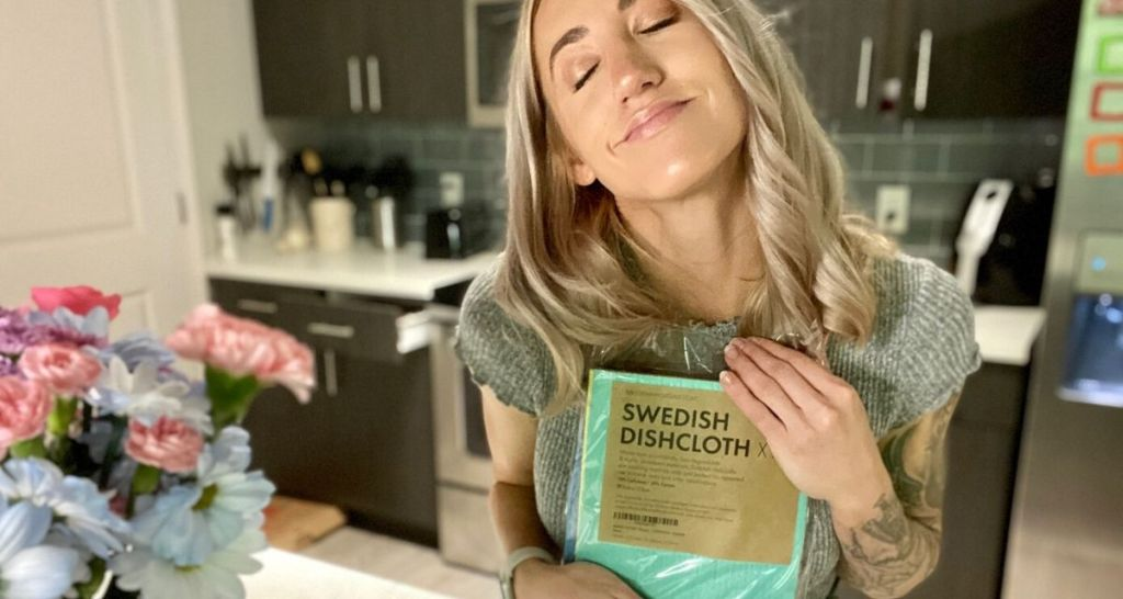 Woman standing over kitchen sink hugging a package of Swedish Dishcloths