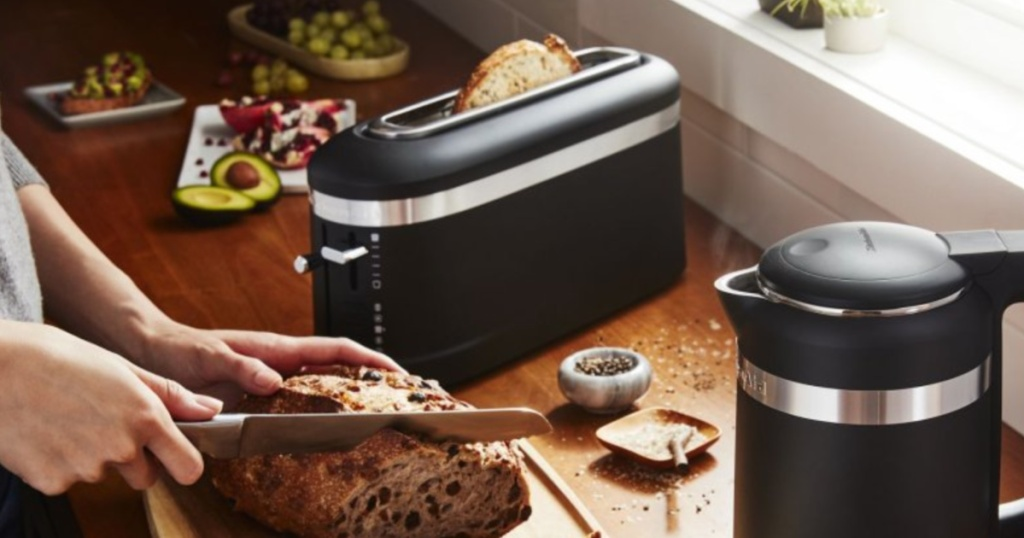 black toaster on kitchen counter and woman slicing bread
