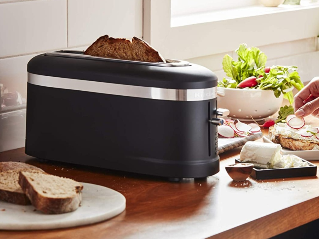 black toaster on kitchen counter with sliced bread and woman cutting food