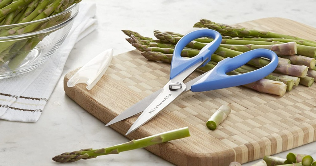 blue kitchenaid brand scissors on cutting board cutting asparagus