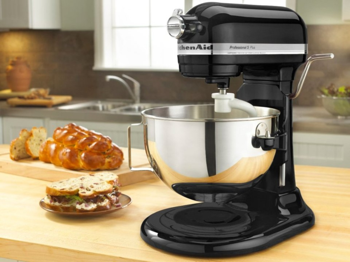 Black Kitchenaid Mixer on wooden counter with bread and sandwich to the left on the counter