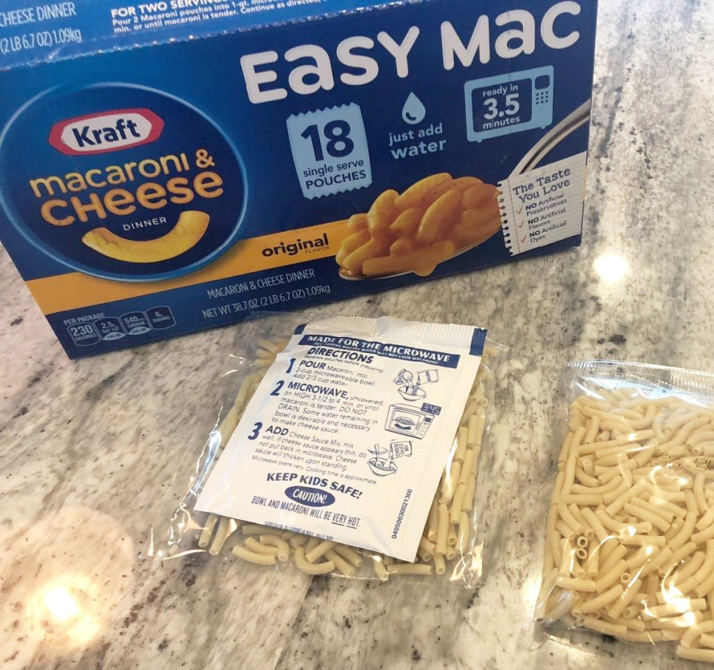 blue box of kraft easy mac packets with packets of dry pasta on kitchen counter